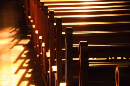 pews in church with light shining through windows