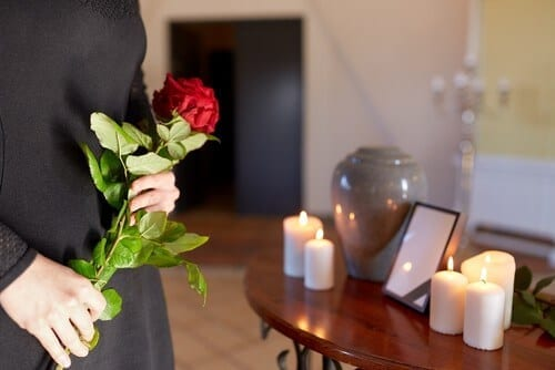 man with roses looking at table with urn and candles