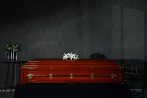Coffin with white flower on top