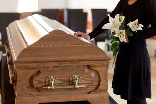 Woman puts hand on coffin